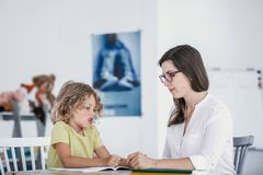 Unhappy child refusing to do exercises from a book with a school royalty free stock images