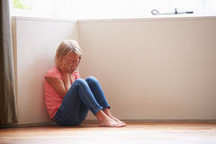 Unhappy Child Sitting On Floor In Corner At Home Royalty Free Stock Photography