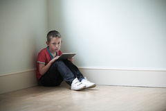 Unhappy Child Sitting In Room With Digital Tablet Royalty Free Stock Image