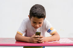 Unhappy child texting on phone Royalty Free Stock Photo