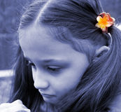 Unhappy child. Young girl with sad expression, looking down. The girl has ponytails with yellow flower. Photo in bluish tone stock photo