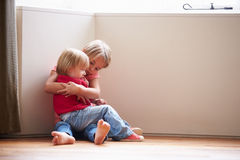Unhappy Children Sitting On Floor In Corner At Home Royalty Free Stock Photos
