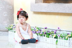 Unhappy Chinese baby girl looks at bubbles in a garden Royalty Free Stock Image