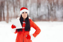 Unhappy Christmas Girl With Pc Tablet. Disappointed Xmas girl with electronic device outside in the snow Royalty Free Stock Images