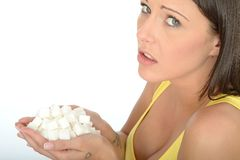 Unhappy Concerned Young Woman Holding a Handful of Unhealthy White Sugar Cubes Stock Photo