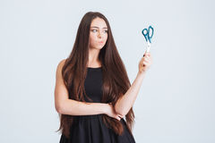 Unhappy confused woman with long hair standing and holding scissors Royalty Free Stock Photo