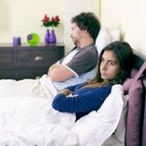Unhappy couple in bed after fight not talking retro style Stock Photography