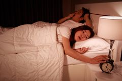 Unhappy couple being awakened by an alarm clock in bedroom in mo Stock Photography