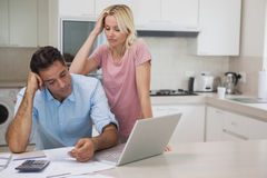 Unhappy couple with bills and laptop in kitchen Royalty Free Stock Images