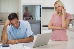 Unhappy couple with bills and laptop in kitchen Royalty Free Stock Photography