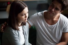 Young man calms unhappy girl at home stock images