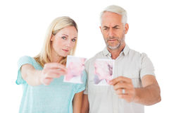 Unhappy couple holding two halves of torn photograph Stock Photography