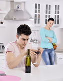 Unhappy couple red vine in the kitchen Royalty Free Stock Images