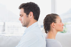 Unhappy couple sitting back to back on the couch Stock Photo