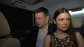 Unhappy couple sitting in car backseat after party, relationship crisis bad date. Stock footage stock video