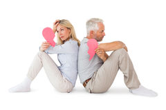 Unhappy couple sitting holding two halves of broken heart Stock Photos