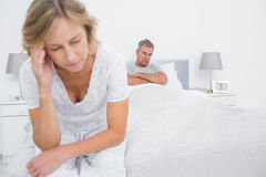 Unhappy couple sitting on opposite ends of bed after a fight. In bedroom at home stock photography