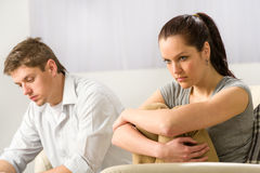 Unhappy couple sitting silently after argument. Unhappy couple sitting on couch silently after argument stock images