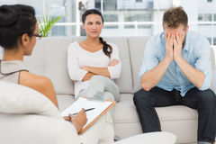 Unhappy couple sitting on sofa at therapy session Stock Images