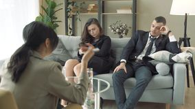 Unhappy couple solving problems in relations visiting family counselor, husband speaking about resentful wife