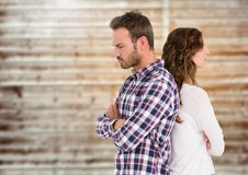 Unhappy couple standing back to back. Against wooden background Royalty Free Stock Image