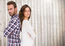 Unhappy couple standing back to back. Against wooden background Stock Photo