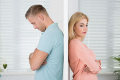 Unhappy Couple Standing Back To Back At Home. Side view of unhappy young couple standing back to back at home Royalty Free Stock Photo