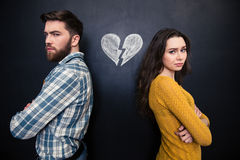 Unhappy couple standing over chalkboard background with drawn broken heart Royalty Free Stock Photo