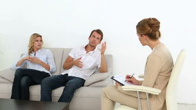 Unhappy couple talking with their therapist. At therapy session stock footage