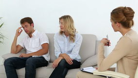 Unhappy couple talking with their therapist. At therapy session stock video footage