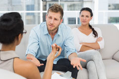 Unhappy couple at therapy session with man talking to therapist Royalty Free Stock Images