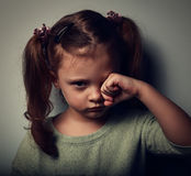 Unhappy crying kid girl in darkness. Closeup Stock Image