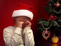 Unhappy crying kid girl in santa claus hat near the Christmas tr Royalty Free Stock Images