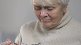 Unhappy crying woman eating tasty porridge in nursing home, feeling homesick stock video