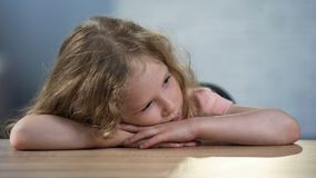 Unhappy curly female kid sitting alone at table, social service for children. Stock photo stock images