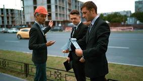 Unhappy customers discontent of architect project. 4k. Ultra HD. Two customers discontent architect work. Text pad. calculations. worker with helmet in suit and stock video footage