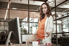 Unhappy dark-haired pregnant lady collecting things for maternity leave. Personal things. Unhappy dark-haired pregnant lady collecting things for maternity leave royalty free stock images