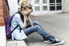 Unhappy Pre teen girl at school. A Unhappy depress Pre teen girl at school Royalty Free Stock Image