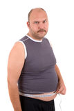 Unhappy dieter. Overweight man looking very unhappy with the measurement of his waist Stock Image
