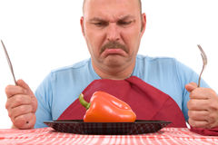 Unhappy dieter. Overweight man with healthy vegetable on plate looking unhappy (focus on pepper stock images
