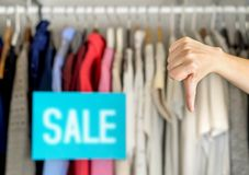 Unhappy customer giving thumbs down in a clothing store. Unhappy and dissatisfied customer giving thumbs down in a clothing store for bad service or product royalty free stock photo