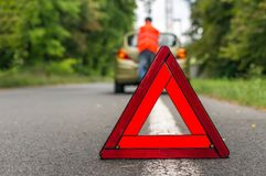 Unhappy driver and broken car on the road. Red warning triangle royalty free stock image