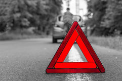 Unhappy driver and broken car on the road. And red warning triangle - black and white concept royalty free stock photography