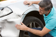Unhappy Driver Inspecting Damage After Car Accident. Unhappy Driver Inspects Damage After Car Accident Stock Photo