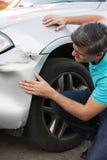 Unhappy Driver Inspecting Damage After Car Accident. Unhappy Driver Inspects Damage After Car Accident stock photos