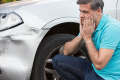 Unhappy Driver Inspecting Damage After Car Accident. Unhappy Driver Inspects Damage After Car Accident stock image