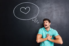 Unhappy embarrassed man crying and having heartache over chalkboard. Unhappy embarrassed young man crying and having heartache over chalkboard background Stock Photo