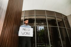 Unhappy executive is looking for job in lobby. Low angle of anxious man needing work. He is standing in business center with paper displaying desire to find new stock images