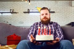 Unhappy fat man with cake birthday  in the room. Unhappy fat man with cake birthday sitting on the couch in the room Royalty Free Stock Photography