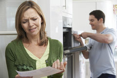 Unhappy Female Customer With Oven Repair Bill Royalty Free Stock Images